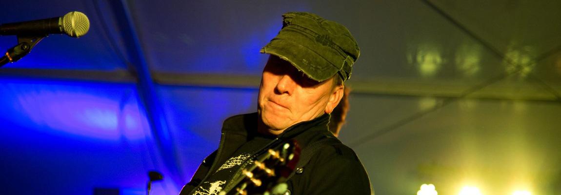 Der Musiker Hartmut Kaukel von Wild@Heart spielt auf einer Bühne Rhythmusgitarre
