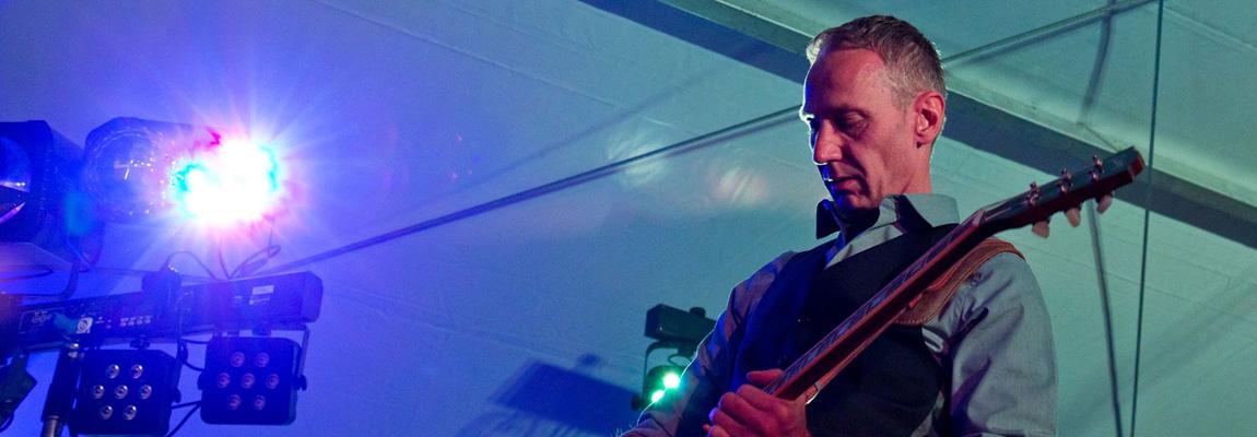 Der Musiker Frank Seidler von Wild@Heart spielt auf einer Bühne Gitarre